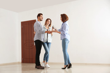 Real estate agent with young couple in new apartment