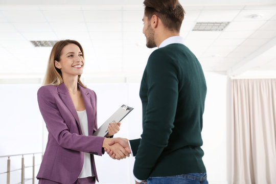 Real estate agent shaking hands with client in new apartment