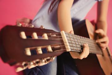 Little girl playing wooden guitar, closeup view