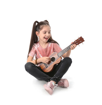 Little cheerful girl playing guitar, isolated on white