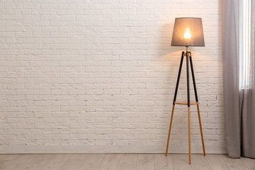 Modern floor lamp against brick wall indoors. Space for text
