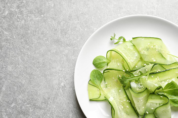 Plate with delicious cucumber salad on grey background, top view. Space for text