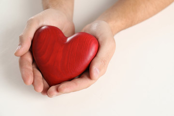 Man holding decorative heart on white background, closeup