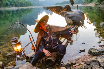 Chinese cormorant fisherman on raft in lake holding a black cormorant bird in Guilin, China.