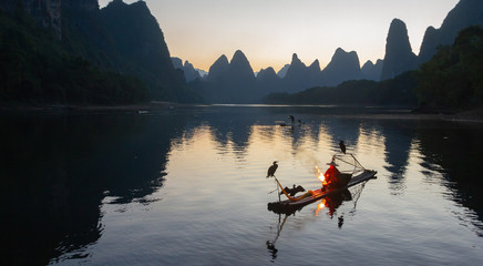 Cormorant fisherman on raft in lake in Guilin, China, with three cormorant birds. Fisherman is using a bright flame to heat teapot and light pipe.
