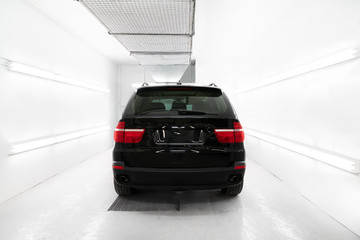Black car in white paint booth