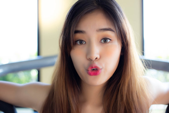 Portrait cheerful woman. Attractive beautiful women act like a kissing someone or making funny face when pretty woman gets happy or good mood. Charming beautiful girl is playful girl and humor person