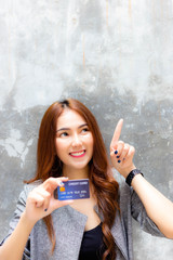 Attractive beautiful woman is pointing finger to copy space above her head and charming beautiful girl show credit card. Gorgeous woman has freedom for paying product, goods, service and satisfy it