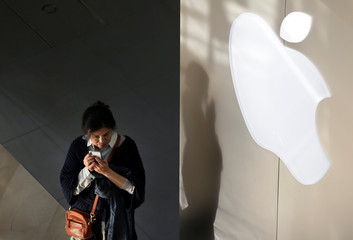 A woman holds her phone near an Apple company logo in Beijing