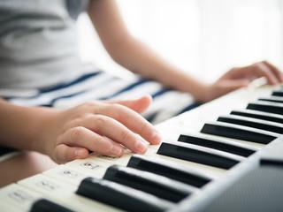 Boy playing keyboard piano near window at home.