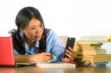 young happy and successful Asian Korean student girl taking selfie self portrait photo with mobile phone studying at laptop computer desk smiling playful