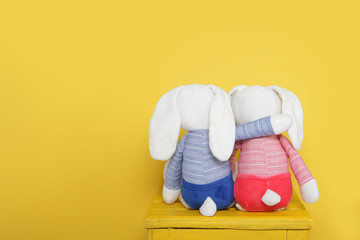 Two cute plush bunnies on yellow background.Rear view