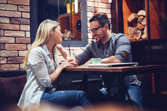 Young attractive couple flirting in cafe.