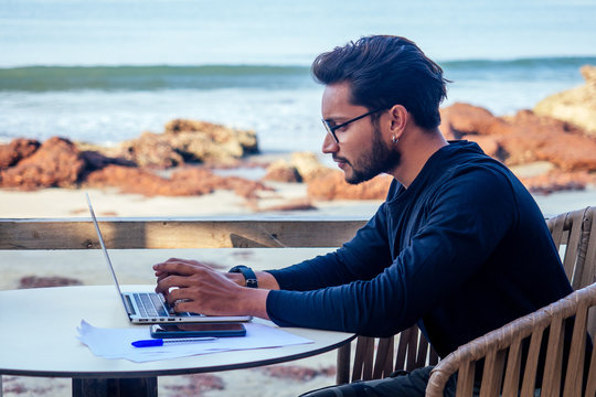 freelancing and remote work.handsome male student working laptop keyboard sitting in cafe on the beach with free internet.Young indian man using computer in summer vacation by the sea