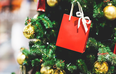 Picture of Christmas tree with gold balls, red packet for gifts.