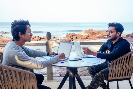 two happy businessmen discussing freelancer strategy in a meeting, Indian business man remote work freelancing sitting in a summer restaurant by the sea.successful deal on the beach tropical island