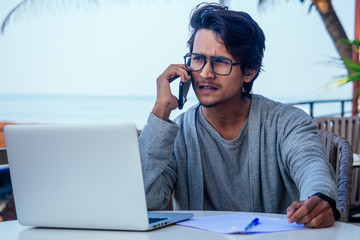 man talking on the phone india summer holidays.stylish young indian male freelancer working with laptop freelance surfing online.businessman at remote work on the beach.dream job.online purchase sale