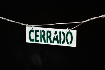 The word closed in the Spanish language on a metal plate.
