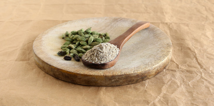 Cardamom powder, a flavoring ingredient, on a wooden spoon, and seeds and pods, on a wooden table.