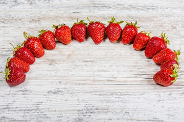 An arc of fresh ripe red strawberries lies on a light textured wooden table. Flatlay, Copyspace