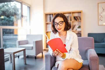 Asian girl student with stylish glasses reading books in the library
