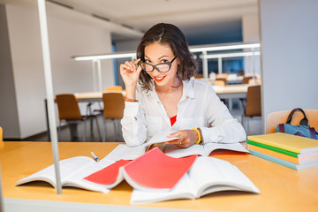young happy teacher with glasses in library checking homework of her students