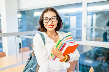 Portrait of a happy girl student or young teacher with backpack and books in university campus