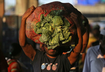A man carries a sack filled with cabbage at a wholesale market in Mumbai