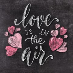 Love is in the air hand drawn chalk lettering on chalkboard background. Valentine's Day holiday illustration.