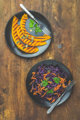 Grilled pumpkin and salad of purple cabbage and carrots on wooden surface