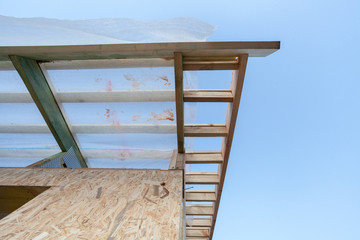Low angle top view eaves of new wooden roof with reliable supports and windproof membrane against blue sky