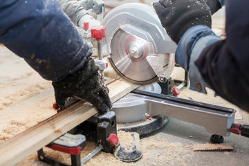 Close up photo of two unrecognizable man using hand electric saw mill to cut part of wooden block