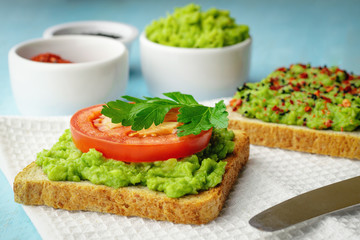 Avocado toasts with a slice of tomato, as well as black sesame and chili peppers and spices in the background