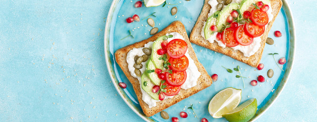 Toasts with feta cheese, tomatoes, avocado, pomegranate, pumpkin seeds and lenseed sprouts. Diet breakfast. Delicious and healthy food. Flat lay. Top view. Banner