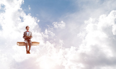 Young businessman or student floating in blue sky and studying the science