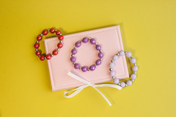 colorful bracelets and pink gift box on yellow background