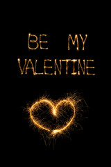 close up view of be my valentine light lettering and heart on black background, st valentines day concept