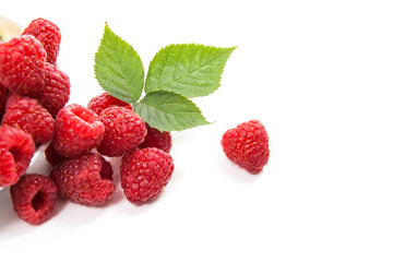 Small plate with ripe raspberries and green leaf isolated on white background.