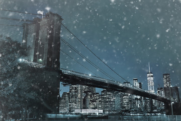 Toned photo of skyscrapers of Manhattan and Brooklyn bridge at snowy winter night