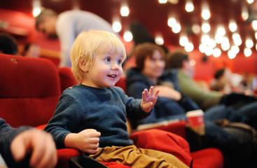 Cute toddler boy watching cartoon movie in the cinema