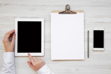 Workspace with tablet, female hands, smartphone and clipboard over white wooden surface, top view. From above, flat lay, overhead. Copy space.