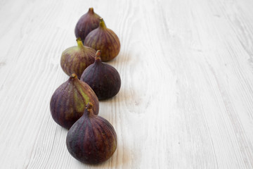 Fresh figs on a white wooden surface, side view. Copy space.
