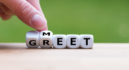 "Hand is turning a dice and changes the word ""Meet"" to ""Greet"""