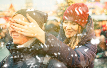 young female close his boyfriend eyes in the street on a winter holidays, surprise concept f