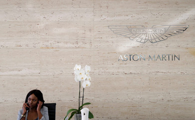 A woman speaks on a phone in front of an Aston Martin logo at Daytona dealership in Sandton