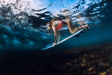 Surfer woman dive underwater with surfboard, under wave.