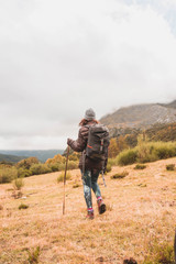 Woman with backpack and cane walking near peak of mountain