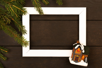 White wooden frame with green natural fir tree branches and toy house
