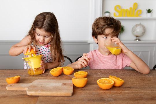Little girl juicing oranges while brother drinks freshly squized orange juice