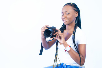 African girl takes pictures. Blacks fashion model. A girl with a sly look. A woman holds a camera in her hands. A woman wants to take a picture. African girl with pigtails.